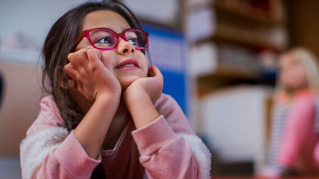 Flicka med rosa glasögon tittar drömmande åt sidan
